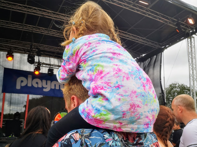 Image of a young girl facing away from the camera and looking towards a large stage that has Playmobil written across it. There is a crowd around her and she is sat on a man's shoulders so she can see above the crowd.