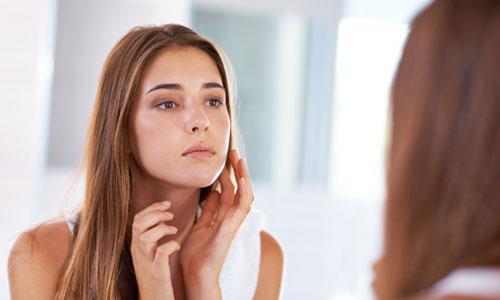 Chica con manchas en la cara mirándose al espejo