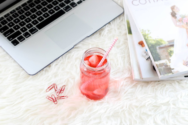 Laptop, books and pink drink displayed on white shaggy rug