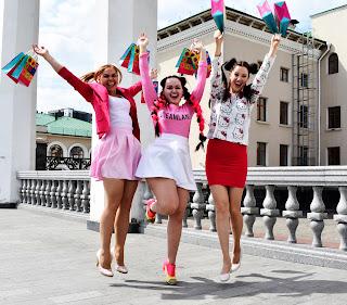 Три девушки в розовом с подарочными пакетами в прыжке