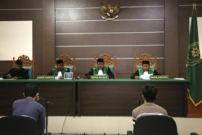 Two men accused of having gay sex sit on the defendants' chairs during their trial at Shariah court in Banda Aceh.
