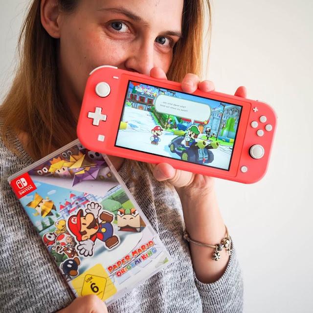 Paper Mario Origami King und Nintendo Switch Lite Konsole in der Farbe Koralle