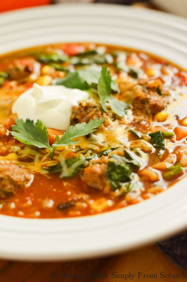 Mexican Meatball Soup garnished with shredded cheddar cheese, a dollop of sour cream  and chopped cilantro in a white soup bowl.