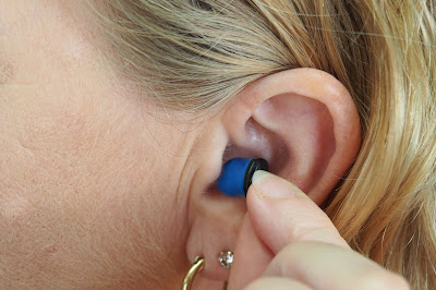 Picture of someone putting an earplug in their ear. Prevent swimmer's ear with ear plugs