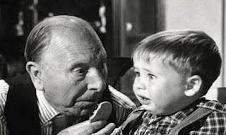 Fotograma en el que el abuelo (Isbert) ofrece una galleta a su desconsolado y pequeño nieto.
