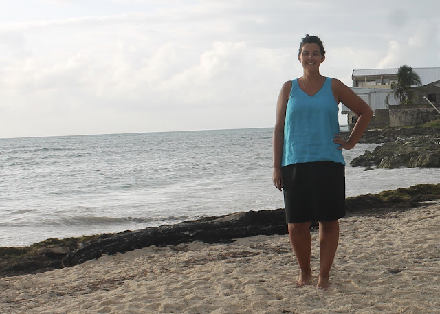 Woman standing on a sandy beach, wearing a turquoise linen tank top hacked from the free Colette Sorbetto sewing pattern.