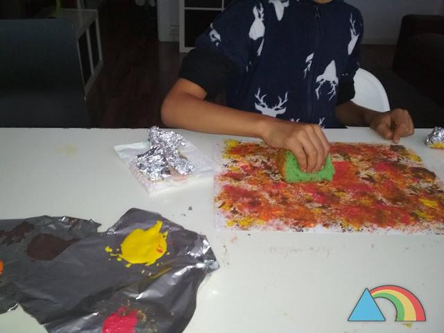 Niño pintando con una esponja sobre una cartulina