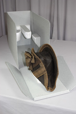 After treatment photo of military chapeau and it's custom made archival storage box. The hat was conserved by textile expert Gwen Spicer at Spicer Art Conservation. SAC conserves and preserves military antiquities, collectibles and memorabilia