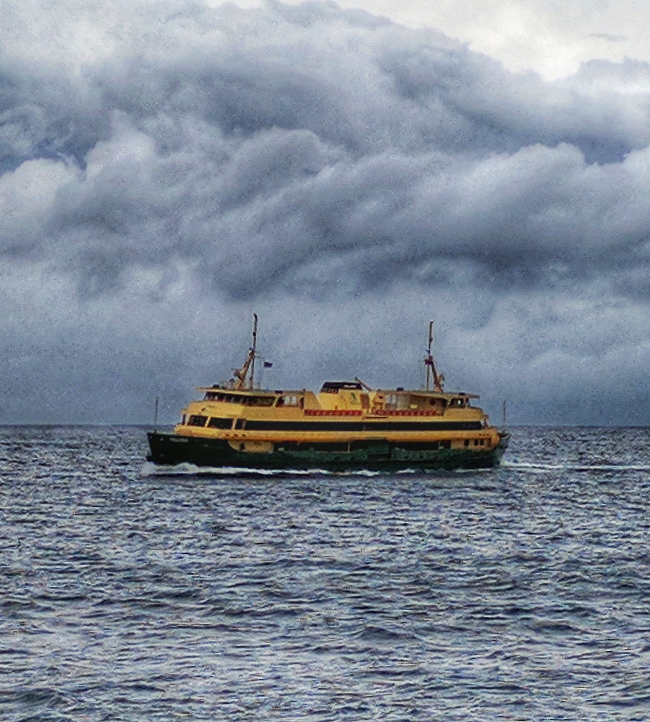 Manly Ferry crossing the Sydney Harbour heads against a cloudy background