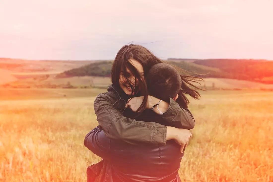 Casal se abraçando no meio de um campo