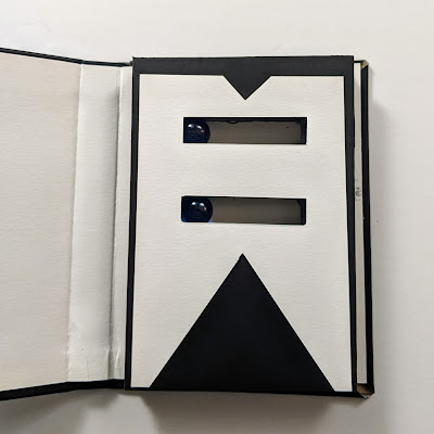 A black and white block style page made on craft board with two horizontal rectangular cutouts, one above the other, containing two moveable marbles going back and forth. The goal would be to simulate a DJ mix by lining up the marbles.