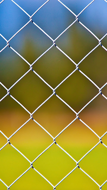 Desktop wallpaper with metal fence and iPhone