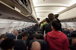 Airplane Passengers Walking Down Narrow Aisle Between Seats
