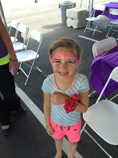 A little girl with her face painted and a balloon lady bug bracelet