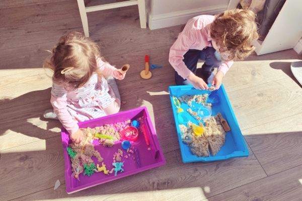 toddler and older sibling playing side by side with activities in seperate trays