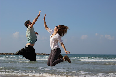 Man and Woman Jumping On Ocean Shore