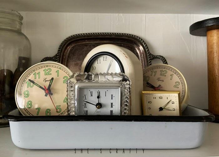 Vintage clocks displayed in an enamel tray in a cupboard.