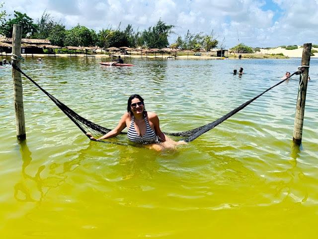 mulher sentada em uma rede dentro da agua de uma lagoa