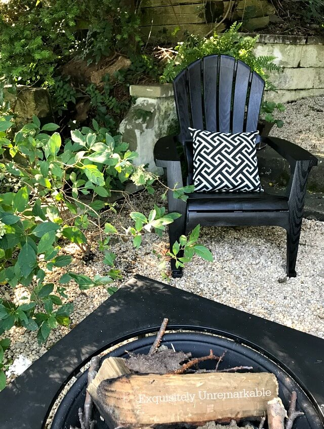 Black Adirondack chair on patio with fire pit