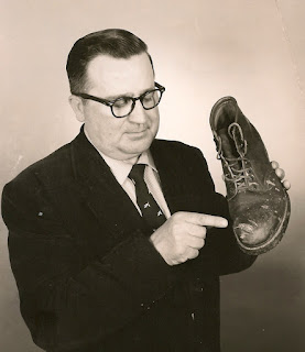 Photo of Wallace B. Dixon pointing to the steel-toe shoe that saved his foot from the lawn mower. Date and photographer unknown. E. Ackemann, 2017.
