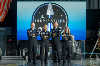 Four crew members standing in front of a large Inspiration 4 logo