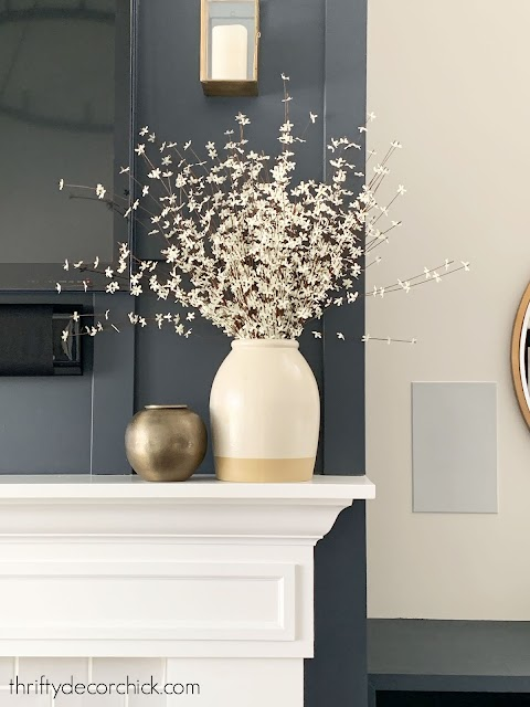 small white flowers in large vase on mantel