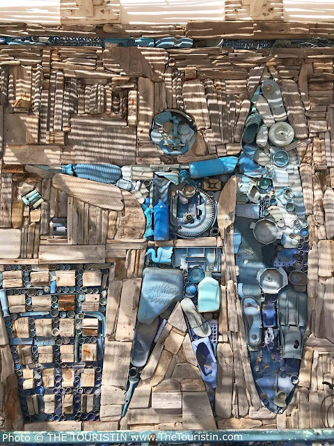 A wall mural of a human and a surfboard made from light blue plastic rubbish.