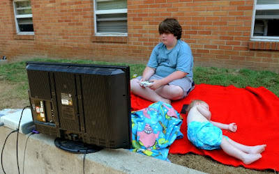 Overweight adolescent boy sits on ground OUTSIDE playing video game on a large television