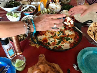 Hands reaching across table filled with Jewish food