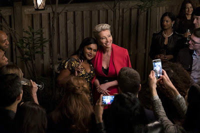 Movie still featuring Mindy Kaling and Emma Thompson hugging at a party surrounded by paparazzi in the movie Late Night