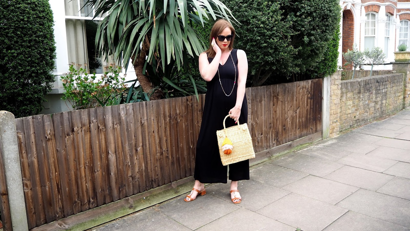 black jumpsuit, brown lobster sandals, straw bag with pom pom