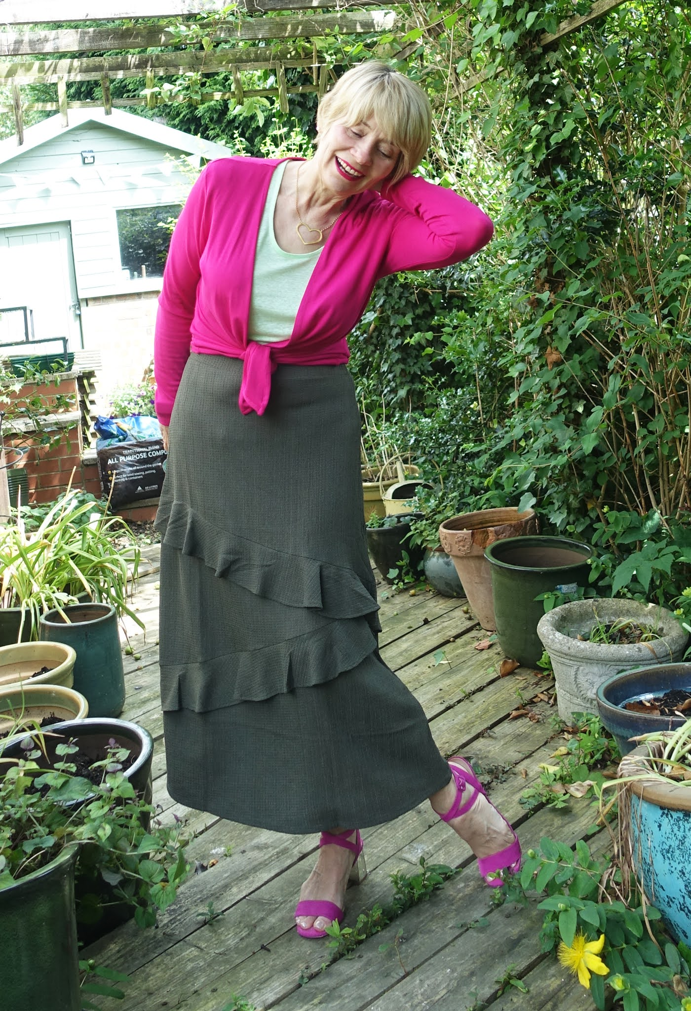 This summer's ruffled midi skirt in olive worn with bright pink and light green by Is This Mutton blogger Gail Hanlon