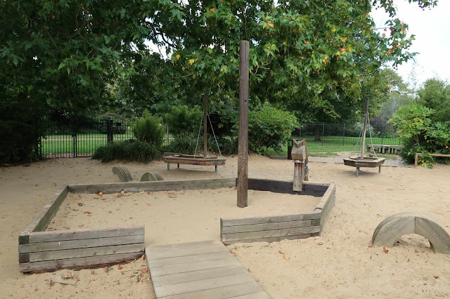 Some wooden boat structures in a sand pit a Diana Memorial Park in London