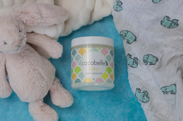 A jar of Cocobelle baby next to a teddy, a muslin and a blanket.