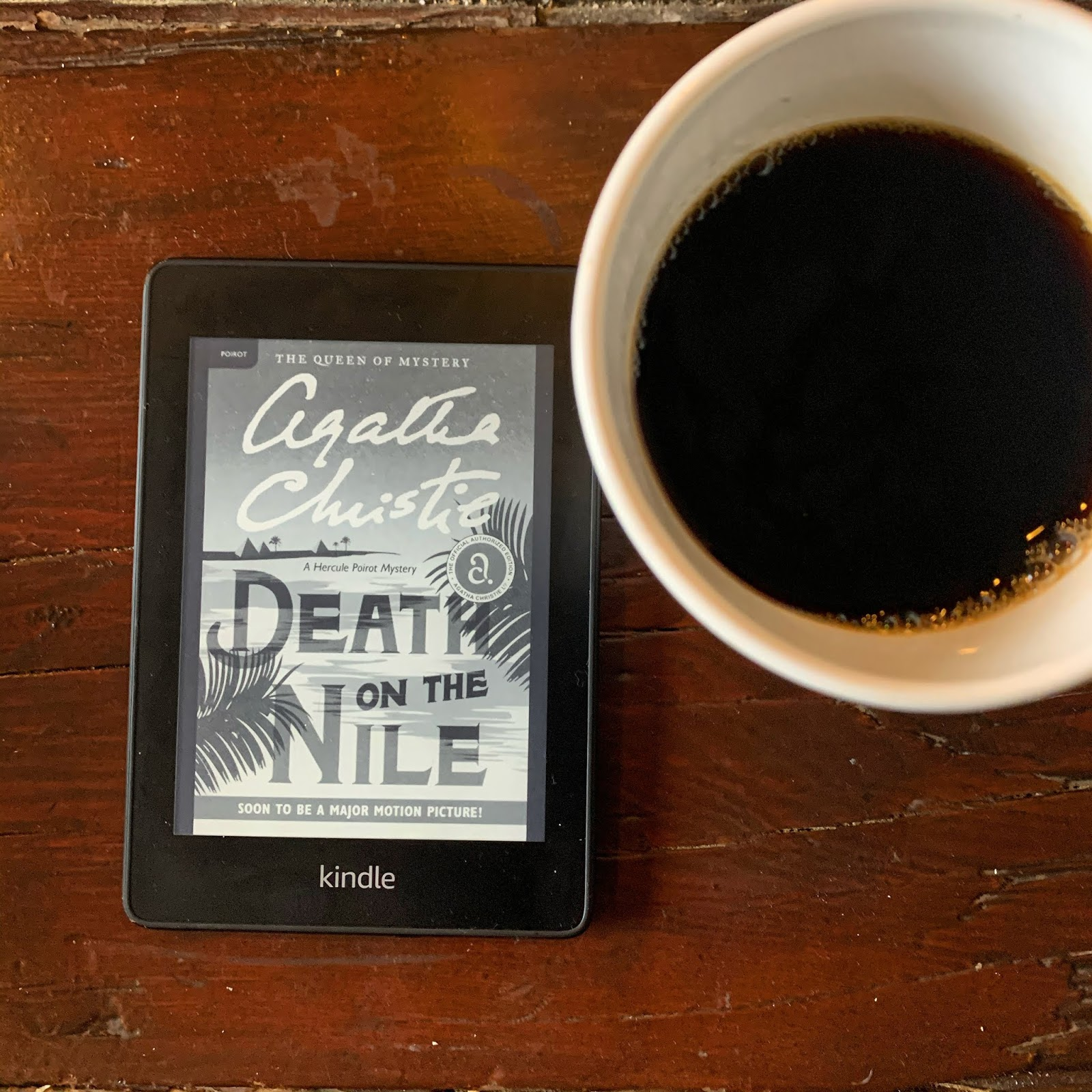 A kindle book with the title page for Death on The Nile by Agatha Christie with a cup of coffee next to it.