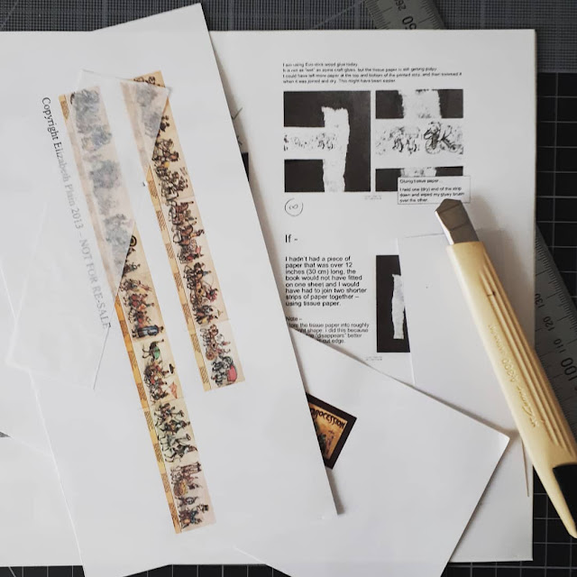 One twelfth scale miniature book kit of a circus procession next to a cutting knife and a ruler