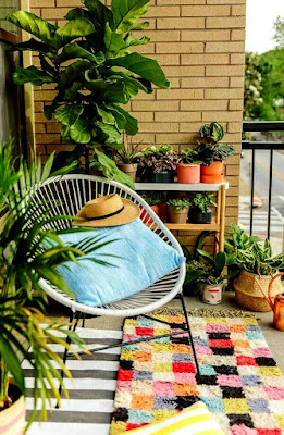 Relaxing balcony design ideas with white chair and pillow on colorful rugs