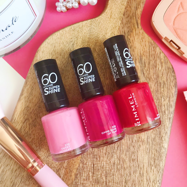 3 Rimmel nail polishes on wooden chopping board. Pastel Pink, Fuschia Pink & Deep Red shades