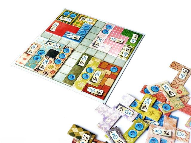 na zdjęciu plansza do gry patchwork a na niej ułożone cztery kwadraty z elementów, obok leży reszta elementów