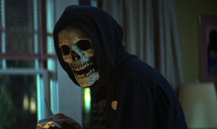 Imagem de capa: uma pessoa encapuzada com um moletom preto, uma máscara de caveira, em um quarto no escuro e uma faca na mão.