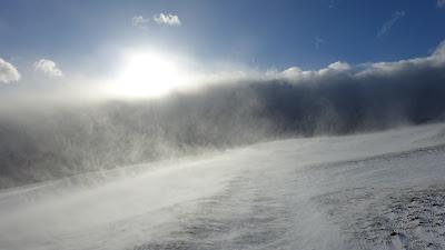Sonne, dunkle Wolken und Schneeverwehungen