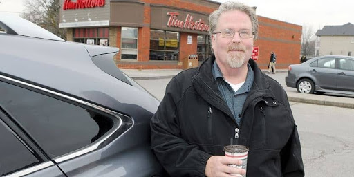 man standing with a cup of coffee in front of tim hortons