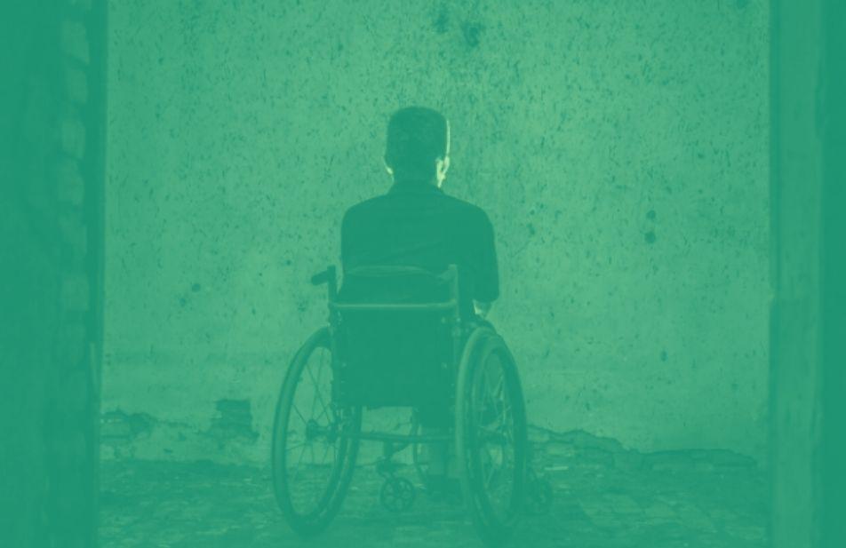 homem na cadeira de rodas triste refletindo de frente para uma parede