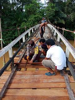 Wujud Kepedulian, Bhabinkamtibmas Polsek Kota Baru Bantu Warga Desa Binaan Perbaiki Jembatan