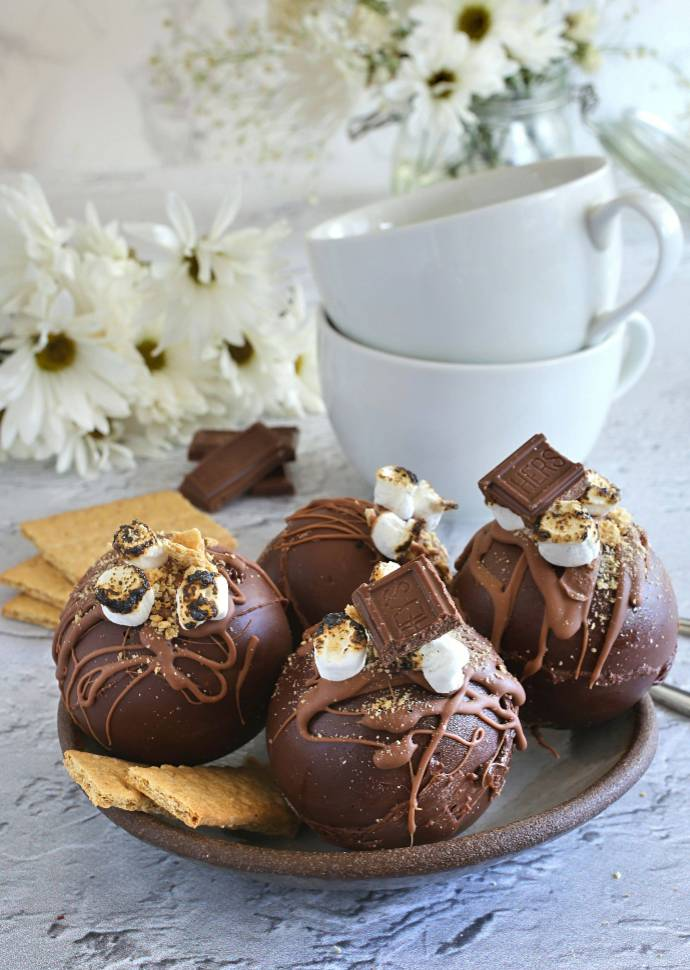 Recipe for hot cocoa bombs made with a milk chocolate shell, filled with hot cocoa mix, mini marshmallows and graham cracker crumbs.