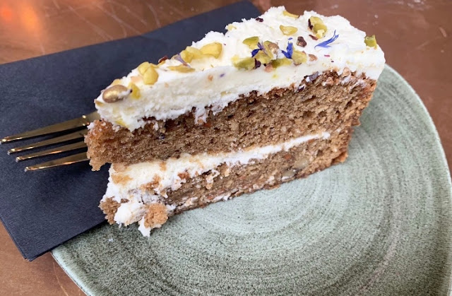 carrott cake on a plate with fork and napkin