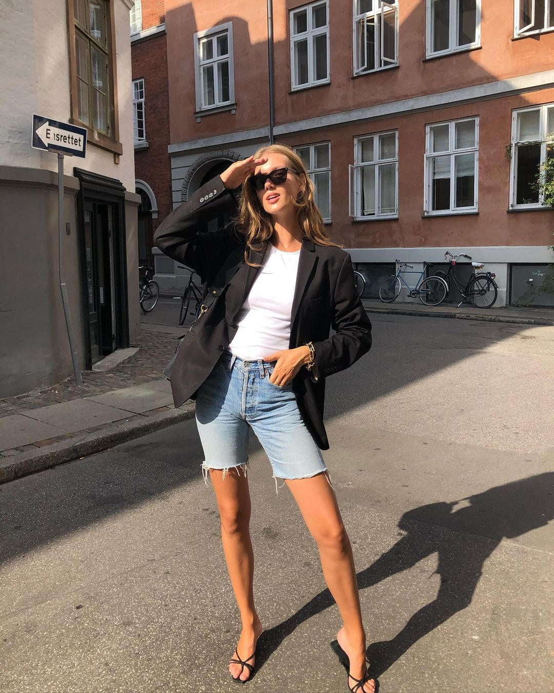 3 Ways to Wear Denim Bermuda Shorts Like an It Girl — Cecilie Moosgaard Nielsen in a black blazer, white t-shirt, long jean shorts, and strappy slide sandals