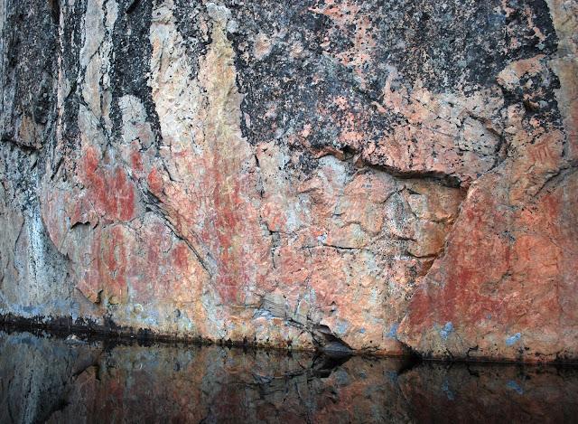 Pysty kallioseinämä, jossa vanha punaisella värillä tehty kalliomaalaus.