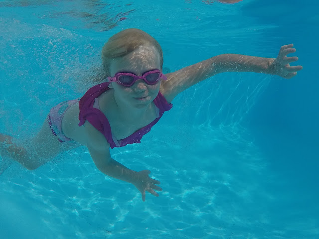 A young girl in bikini swimming underwater on holiday in France