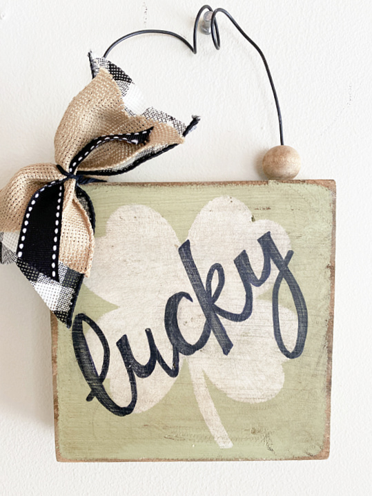 cursive lucky sign with bow and wire hanger